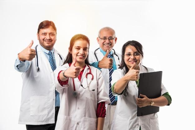 成功または親指を立てるサインを示すインドのアジアの医師の集合写真。白い背景の上に孤立して立っています。セレクティブフォーカス