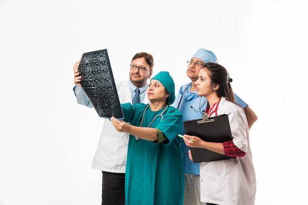 흰색 배경 위에 격리된 엑스레이 또는 mri를 찾고 있는 인도 아시아 의사. 선택적 초점