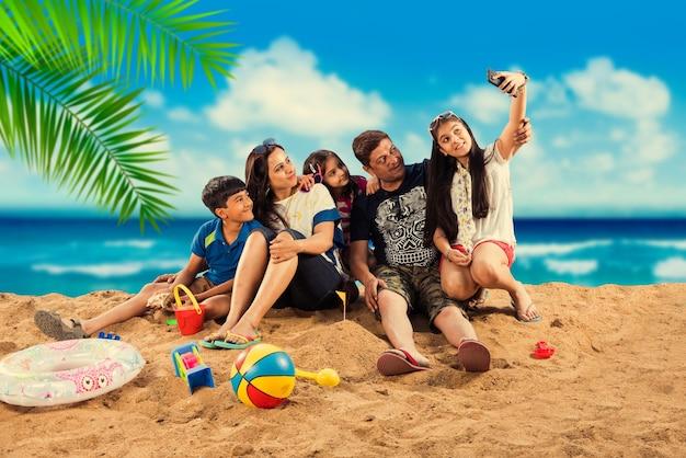 夏にビーチで楽しむインドのアジアの家族