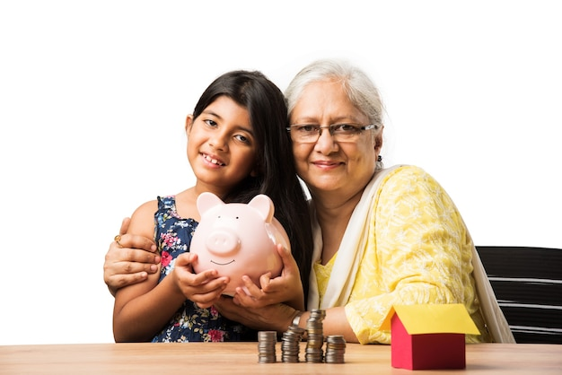 Indian or asian grandma teaching cute grand daughter importance of savings, putting coins into pink piggy bank
