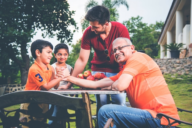 Indian asian kid and grandfather arm wrestling and having fun