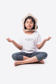 白い背景の紙の家のモデルを保持しているインドのアジアの少女-家&家族の概念