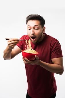 箸で赤いボウルに熱い麺やラーメンを食べるインドのアジア人男性