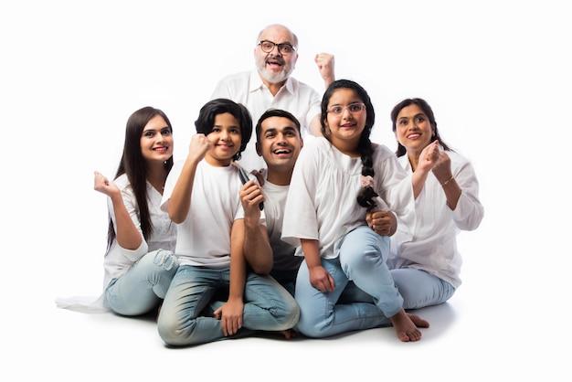 Индийская азиатская многопоколенная семья из шести человек смотрит телевизор вместе дома и веселится, сидя на полу на белом фоне