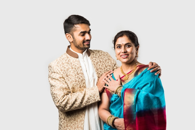 Indian asian old mother and adult son in traditional wear standing isolated over white wall