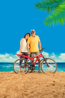 Indian asian retired couple with their bike or bicycle on the beach, moody effect
