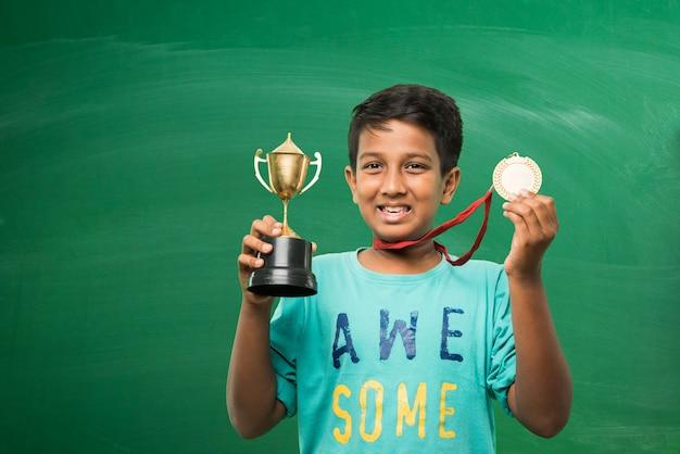 녹색 칠판 배경 위에 금 트로피 컵을 들고 있는 인도 아시아 학교 아이들