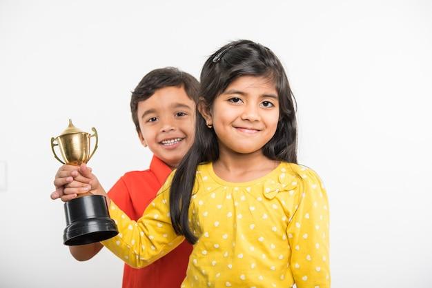 흰색 배경 위에 금 트로피 컵을 들고 인도 아시아 학교 아이들