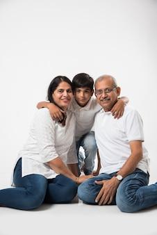 Индийская азиатская старшая пара или дедушка и бабушка с внуком, изолированные на белом