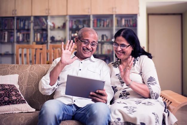 인도 아시아 노인 부부는 집에서 소파나 정원에 앉아 태블릿 컴퓨터로 화상 채팅을 하고 선별적인 초점을 맞춥니다.