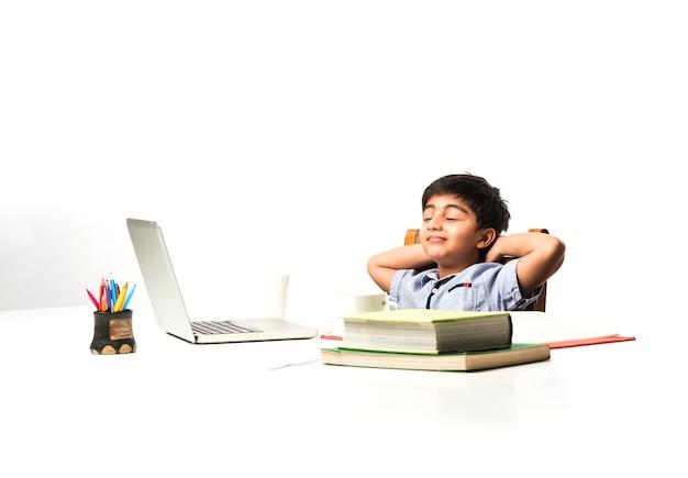 Индийский азиатский маленький ребенок устал от учебы, поэтому растягивается или дремлет за учебным столом дома