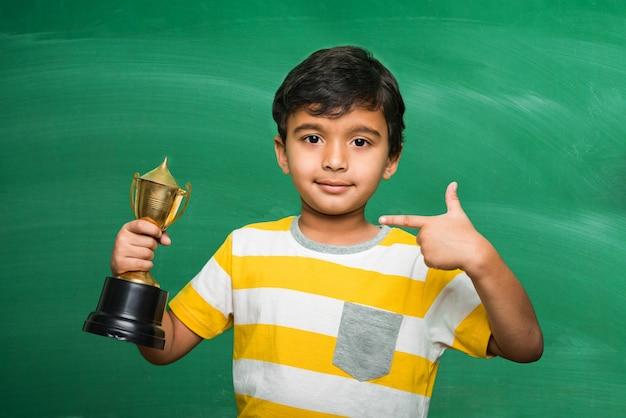 흰색 또는 녹색 칠판에 트로피 또는 우승 컵을 들고 인도 아시아 작은 학교 아이