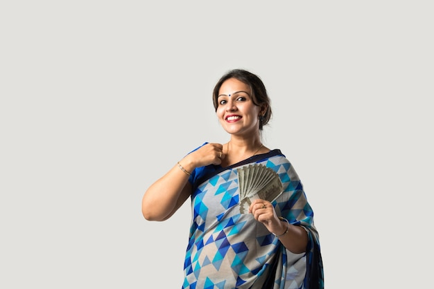 白い壁に紙幣や扇子を表示または保持しているサリーまたはサリーのインドのアジア人女性