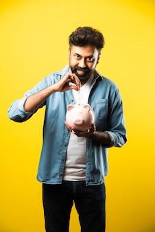 黄色の貯金箱を保持しているインドのアジアの若いひげを生やした男。人と金融の概念