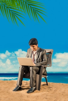 Indian asian young businessman relaxing or working from beach enjoying break from work