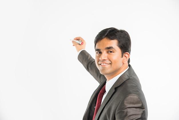 白い背景の上に分離されたマーカーペンで空中で書くインドのアジアの青年ビジネス