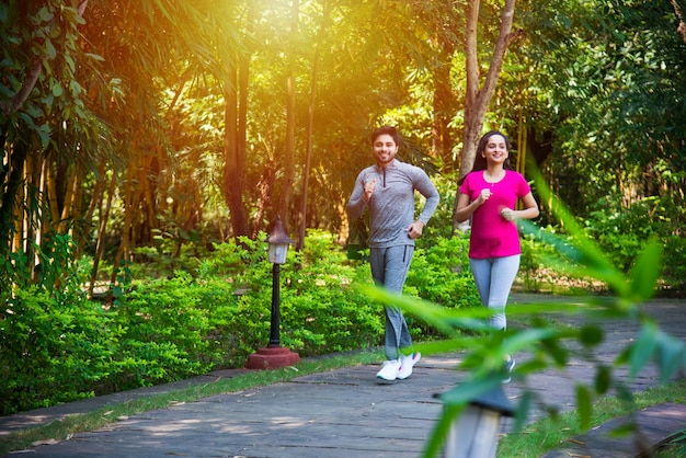 インドのアジアの若いカップルが公園や自然の中で屋外で運動やストレッチを実行してジョギング