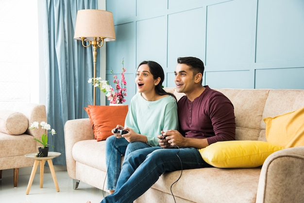 Indian asian young couple playing video game using joystick or controller while sitting on couch or sofa