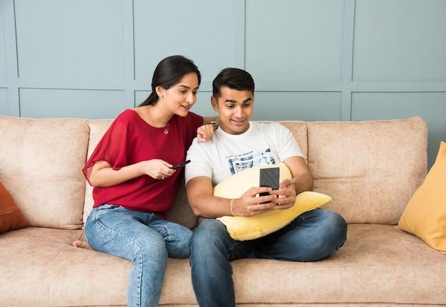 Индийская азиатская молодая пара вместе использует смартфон, сидя на диване или диване и в современном интерьере или доме