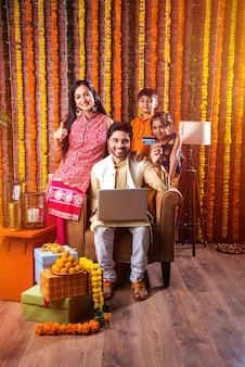 Индийская азиатская молодая семья делает покупки онлайн в ночь фестиваля дивали с электронной картой и ноутбуком