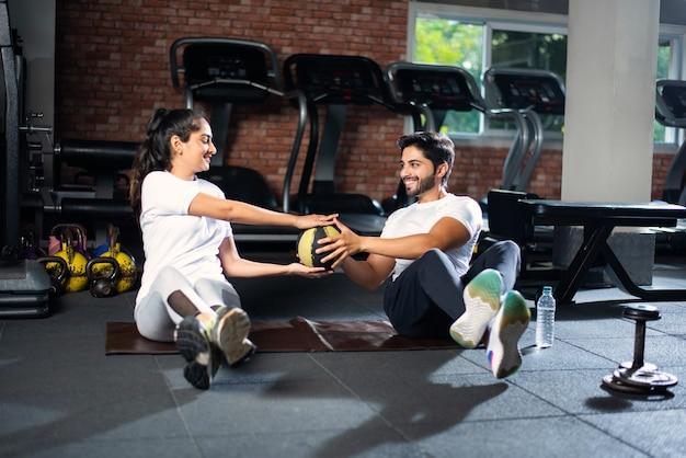 바닥에 요가 매트에 서로 공을 전달하는 연습을 하 고 인도 아시아 젊은 맞는 커플.