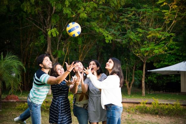 サッカー、サッカー、バレーボールをして応援しているインドのアジアの若い友人