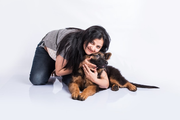 Indian or asian young lady playing with german shepherd puppy isolated on white background