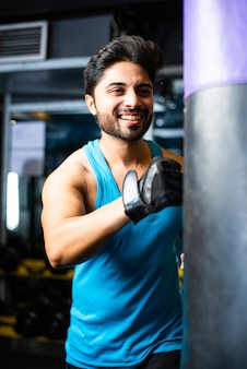 Indian asian young man boxing in gym with punching bag with gloves on