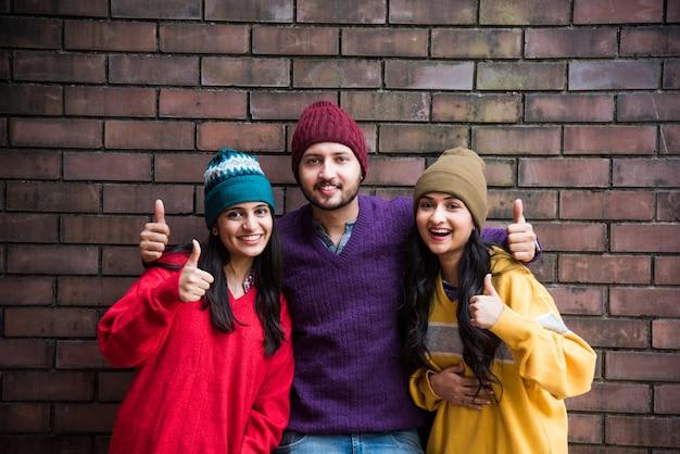인도 아시아 젊은 모델 또는 화려한 모직 스웨터와 모자를 입고 포즈를 취하는 친구