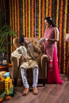 Индийская привлекательная пара в традиционной одежде празднует фестиваль дивали, день рождения или годовщину с подарками-сюрпризами и сладким ладду на фоне украшенных цветами календулы