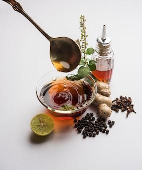 Индийская аюрведическая кадха или карха, или тоник для здоровья, или напиток для борьбы с короной, сезонными инфекциями, сделанный с использованием имбиря, тулси, черного перца, гвоздики и меда.