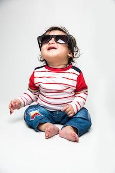 白い背景の上に分離された、暗い眼鏡、サングラス、またはゴーグルを着用しようとしているインドの男の子または幼児