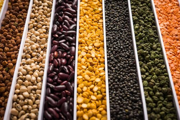 Индийская фасоль, бобовые, чечевица, рис и зерно пшеницы в белом ящике с ячейками или полосками, выборочный фокус.