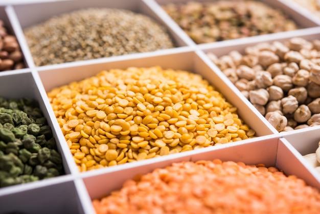 Индийская фасоль, бобовые, чечевица, рис и зерно пшеницы в белом деревянном ящике с клетками, выборочный фокус.