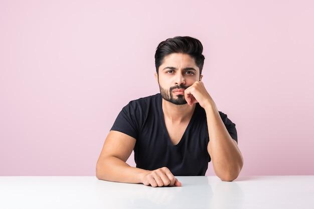 テーブルや机の上のピンクの背景に対して孤立して座って考えているインドのひげを生やした若い男