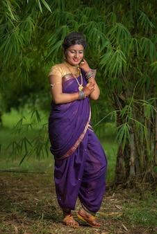 屋外でポーズをとる伝統的なサリーのインドの美しい少女