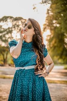 Индийская красивая молодая девушка с длинными волосами в парке с синим коротким платьем и солнцезащитными очками