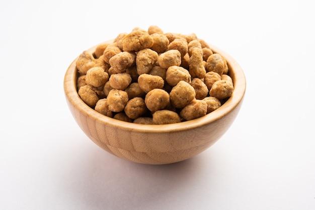 인도 besan 코팅 바삭하고 매운 마살라 땅콩 또는 mungfali가 그릇 또는 접시에 제공됩니다.
