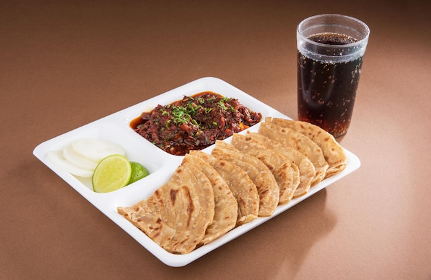 Indian bhuna mutton or gosht  or lamb curry served with roti or chapati in white plate over colourful background