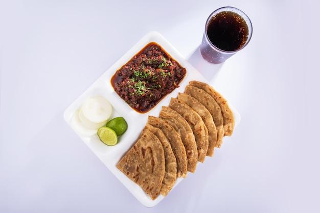 인도 bhuna mutton 또는 gosht 또는 양고기 카레는 화려한 배경 위에 흰색 접시에 roti 또는 chapati와 함께 제공됩니다.