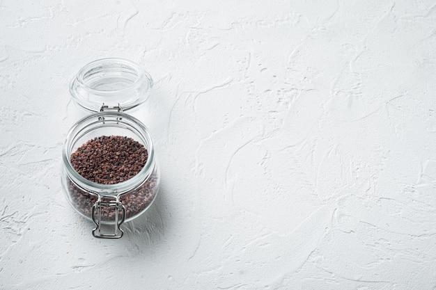 Индийская черная соль, концепция здорового питания кала намак хинди, в стеклянной банке, на белом камне