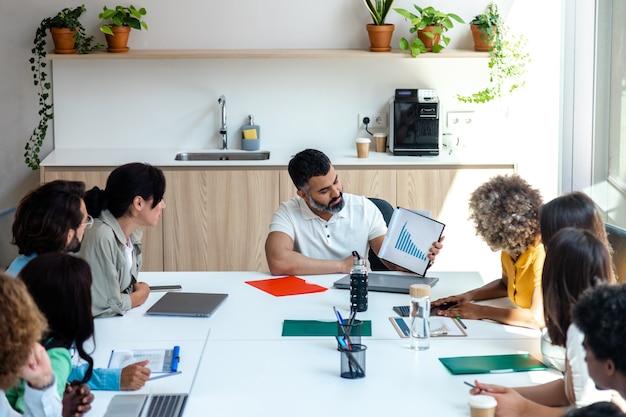 インドのボスがオフィスの従業員にビジネスの進化のグラフを表示コピースペースビジネス会議