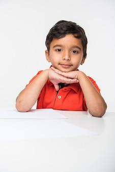 Индийский мальчик, использующий красочный карандаш для рисования или учебы с глобусом и увеличительным стеклом, сидит за белым столом