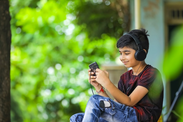 Indian boy listening music or learning on mobile phone