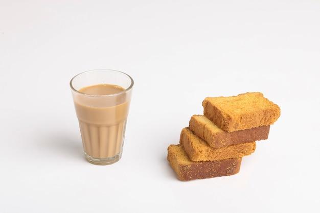 インドの朝食。白い背景の上のお茶とラスク。