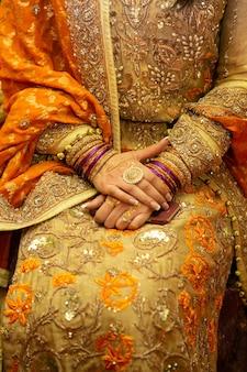 Индийский наряд невесты с золотыми украшениями из хны и платье с вышивкой крупным планом