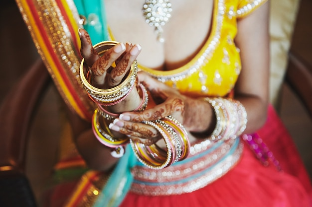 Indian bride wear saree putting the bracelets on hand with mehndi