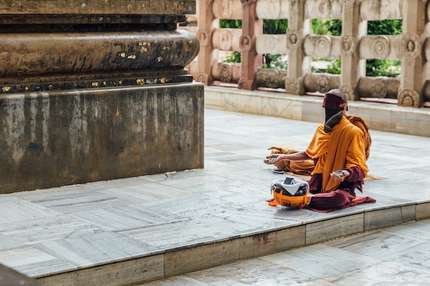 Indian buddhist monk in meditation near the bodhi tree near mahabodhi temple while raining at bodh gaya, bihar, india.
