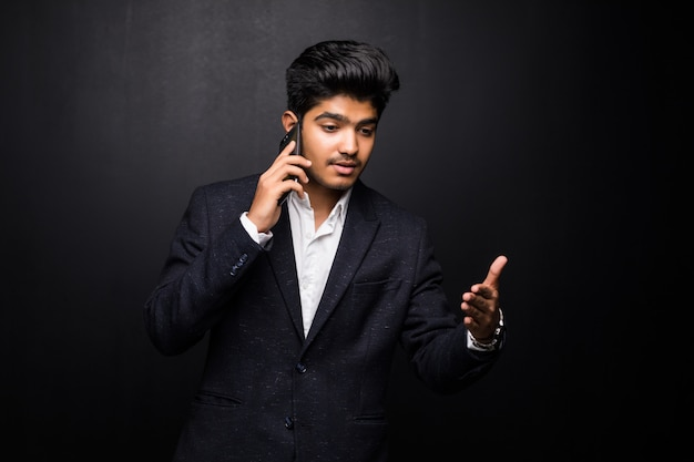 Indian business man talking on phone on black wall