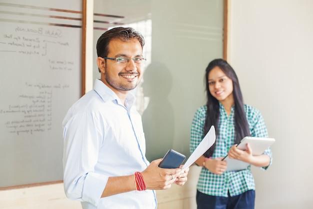 서서 카메라를 보고 있는 두 사람의 인도 비즈니스 팀